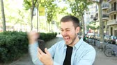 hír : Excited man uses a smart phone and finds amazing content. Then looks at camera