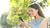 dziewczyna : Happy woman browses smartphone online content in a sunny day