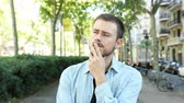indifferent : Front view of a suspicious man listening to you doubting in the street
