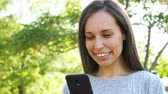 dziewczyna : Close up of a happy adult woman using smart phone in a park