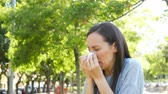 dziewczyna : Ill woman sneezing and blowing on wipe standing outdoors in a park