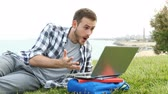 hír : Surprised student using a laptop finds amazing content online lying on the grass Stock mozgókép