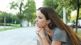 dziewczyna : Serious pensive woman contemplating sitting on a bench in the street
