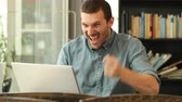 gebot : Excited man using a laptop celebrating good news sitting in a coffee shop