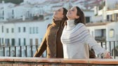 oddech : Two happy friends breathing deep fresh air in winter in a balcony in a rural town