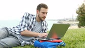 accademia : Serious student e-learning using a laptop lying on the grass