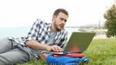 Sad student checking grades online with a laptop sitting on the grass