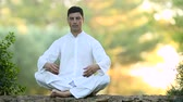 soul searching : Young latin man sitting on the wall and meditating, selective focus Stock Footage