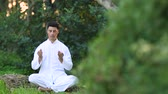 soul searching : young latin men in white clothing doing meditation in the nature