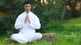 soul searching : Serene young man sitting in the park doing meditation Stock Footage