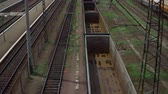 sleepers : railway tracks, freight train with empty cars, the camera rises, in the background the station and the railway goes away, there are electric poles and hanging wires Stock Footage