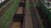 sleepers : railway tracks, freight train with empty cars, the camera rises, against the background of other trains and the railway goes away, there are electric poles and hanging wires. Tanks and locomotives