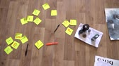 On the wooden floor are stickers, pens, books. Close up. working environment Wideo