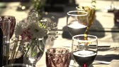 tatma : On the table are glasses of wine, flowers. Close-up shows glasses of wine illuminated by natural sunlight. Wine tasting.