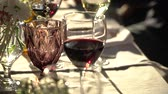 On the table are glasses of wine, flowers. Close-up shows glasses of wine illuminated by natural sunlight. Wine tasting.