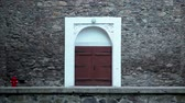 closed : Wooden door of an old stone building. brown wooden, double door with white stone wall edging. Stock Footage
