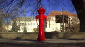 güvenli : Red fire hydrant on the street. People walk down the street. Clear autumn day, clear sky. fire hydrant on the background of the fence and the building Stok Video