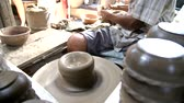 wazon : Close-up shot of half-finished ceramic vase spinning on potterss wheel and hands molding clay with professional tools