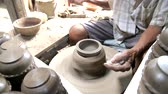 花瓶 : Close-up shot of half-finished ceramic vase spinning on potterss wheel and hands molding clay with professional tools