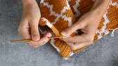 crocheting : young womans hands crocheting with orange and white cotton thread on stone table background, top view close-up full HD stock video footage in real-time Stock Footage