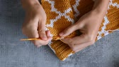 skein : adult girls hands crochet hook with orange and white cotton threads on stone tabletop background, view from above close-up full HD stock video footage in realtime