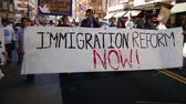 legalize : Immigration Reform Banner. A large white picket banner that reads, Immigration Reform Now! is held up and carried by multiple people during an immigration rally in downtown Los Angeles on September 22, 2013. Stock Footage