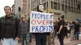 PEOPLE OVER PROFITS Sign. Protester wears a vendetta mask at an Occupy Rally in downtown Los Angeles, California on May 1st, 2012.