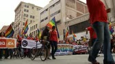 people protesting : Los Angeles LGBTQ Rally. Protesters and immigrants with rainbow flags and banners march for gay pride in downtown Los Angeles, California on May 1st, 2012. Stock Footage