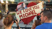 king of pop : Fans Photograph Wreath. Flower arrangement reads WE LOVE YOU MICHAEL outside Michael Jacksons memorial service at LA LiveStaples Center in downtown Los Angeles, California on July 7th, 2009. Stock Footage