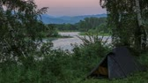 Tourist tents. Sunset, Spring flood in the river Yenisei. Sayanogorsk, Republic of Khakassia, Russia, Full HD.