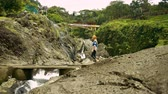 torrente : Young woman walking stone bridge across stream in front of waterfalls in Baturraden, Indonesia
