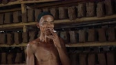 zastřešení : Portrait of old indonesian man smiling with one tooth smoking in clay roof tile making factory in Kebumen, Indonesia - editorial