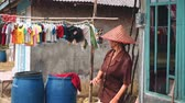 wieszak : Mature indonesian woman dancing in front of house and drying clothes in rural village in Indonesia, Java island