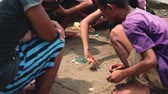 pobre : Children play game of marbles on ground, Indonesia
