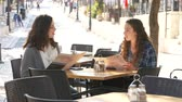 metáfora : Two girls sitting at a cafe, looking in menus Stock Footage