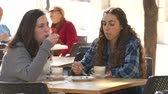 metáfora : Teenage girls sitting in a cafe, drinking coffee and eating a cake