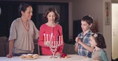 judaico : Kids and their mother lighting Hanukka candles