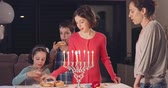 judaico : Kids and their mother eating donuts with a menora and dreidels