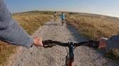 faaliyetler : POV of two kids enjoying a bicycle ride on the countryside with their father Stok Video