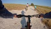 parques : POV of two kids enjoying a bicycle ride on the countryside with their father Stock Footage