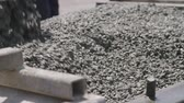 Workers pouring concrete into large steel molds on a construction site Wideo