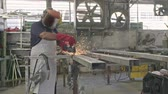 溶接機 : Slow motion of a worker using metal grinder with sparks flying at a metal shop