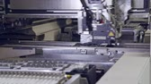 componente : Automated SMT machine placing electronic components on a board.