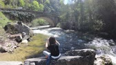 solitário : young woman alone at the edge of a river taking photographs with her phone, Pyrenees in the south of France Stock Footage