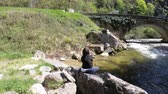 solitário : young woman alone at the edge of a pyrenean river, Aude in southern of France