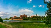 polsko : 4K - timelapse. View of a medieval castle in Malbork with a reflection in the river.