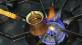 turečtina : Making turkish cofee in copper cezve over gas stove.