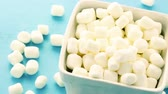 dezert : Small round white marshmallows on blue backgrouns. Dostupné videozáznamy