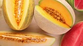 miniatura : Variety of organic melons sliced on wood table.