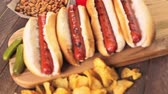 pepinos : Grilled hot dogs on a white hot dog buns with chips and baked beans on the side. Vídeos